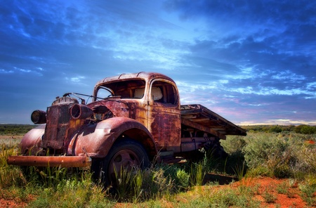 A rusty old pick-up truck sits derelict in a field photo