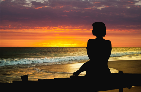 Silhouette of woman sitting at the beach at sunset at sunset