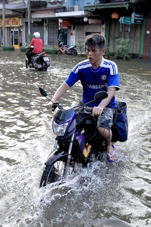 17 20: BANGKOK, THAILAND - NOVEMBER 17 : Motorbike navigates the floods after the heaviest rains in 20 years in Thailand on Nov 17, 2011 in Bangkok, Thailand Editorial