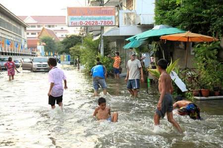 banglumpu: BANGKOK, THAILAND - NOVEMBER 17 : Kids playing in flood water in Bangkok after the heaviest rains in 20 years in Thailand on Nov 17, 2011 in Bangkok, Thailand