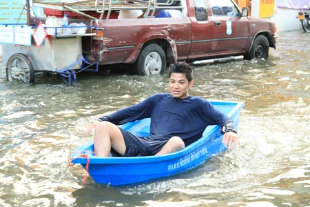 BANGKOK, THAILAND - NOVEMBER 17 : Man in emergency boat after the heaviest rains in 20 years in Thailand on Nov 17, 2011 in Bangkok, Thailand Stock Photo - 11249836