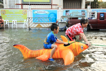 banglumpu: BANGKOK, THAILAND - NOVEMBER 17 : Boy Plays in floods after the heaviest rains in 20 years in Thailand on Nov 17, 2011 in Bangkok, Thailand