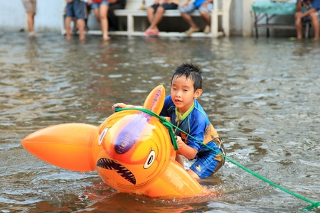17 20: BANGKOK, THAILAND - NOVEMBER 17 : Boy Plays in floods after the heaviest rains in 20 years in Thailand on Nov 17, 2011 in Bangkok, Thailand