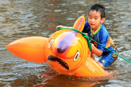 BANGKOK, THAILAND - NOVEMBER 17 : Boy Plays in floods after the heaviest rains in 20 years in Thailand on Nov 17, 2011 in Bangkok, Thailand