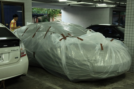soi: BANGKOK, THAILAND - NOVEMBER 17 : Car wrapped in protective plastic after the heaviest rains in 20 years in Thailand on Nov 17, 2011 in Bangkok, Thailand