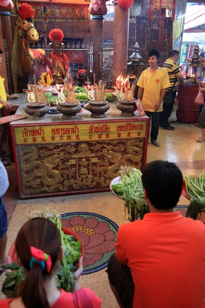 BANGKOK - JANUARY 23 : Chinese New Year 2012 - People make offerings to god in temple in Chinatown, Bangkok, Thailand