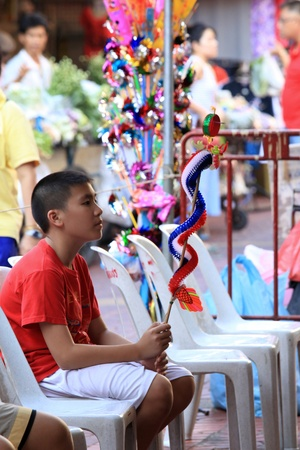 BANGKOK - JANUARY 23 : Chinese New Year 2012 - Boy sits holding dragon in Chinatown, Bangkok, Thailand