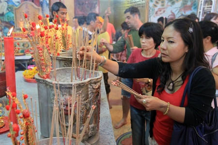 BANGKOK - JANUARY 23 : Chinese New Year 2012 - Woman places incense stick in temple in Chinatown, Bangkok, Thailand Stock Photo - 12060205