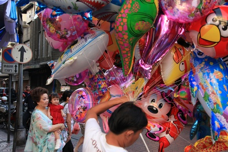 BANGKOK - JANUARY 23 : Chinese New Year 2012 - Young girl amazed by balloons in Chinatown, Bangkok, Thailand