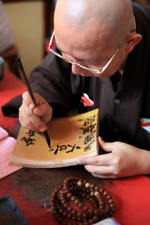 Monk writing calligraphy at Kek Lok Si Temple in Penang, Malaysia photo