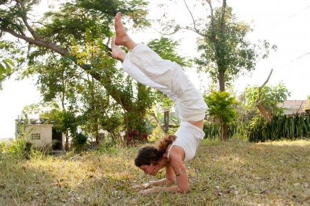 Yoga female master with perfect balance practices scorpion position photo