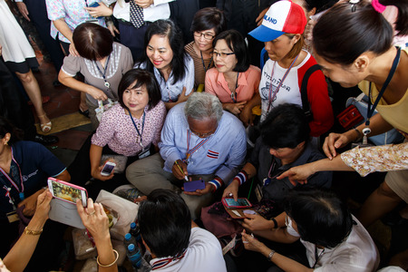 the autograph: BANGKOK - APRIL 3 2014: Leader Suthep Meets supporters and signs autograph for protesters near Rama 8 Bridge in Bangkok, Thailand