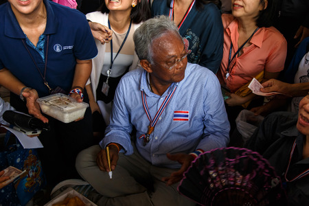 BANGKOK - APRIL 3 2014: Leader Suthep takes money from supporters and signs autograph for protesters near Rama 8 Bridge in Bangkok, Thailand Stock Photo - 27171607