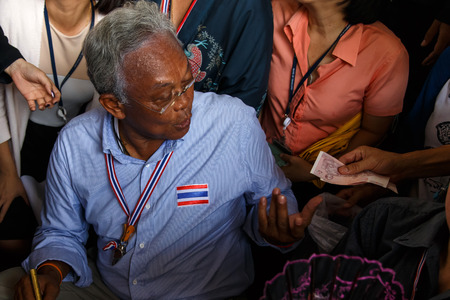 BANGKOK - APRIL 3 2014: Leader Suthep takes money from supporters and signs autograph for protesters near Rama 8 Bridge in Bangkok, Thailand Stock Photo - 27171608