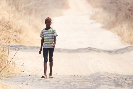CHOBE, BOTSWANA - OCTOBER 5 2013: Poor African child wander through the desert like Chobe National Park. This year was declared as a drought year by the government in Botswana, Africa