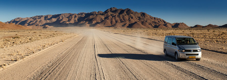 SUSSUSVLEI, NAMIBIA - NOVEMBER 2 2013: Tour Mini Van continues through the Namib Desert National Park in a year that was declared as a drought year by the government in Namibia, Africa
