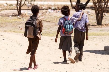 niños caminando: Katima Mulilo, NAMIBIA - 16 de octubre de 2013: La vida local continúa durante un año de sequía en la ciudad nororiental de Katima Mulilo en Namibia, África
