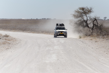 ETOSHA, NAMIBIA - OCTOBER 27 2013: Safari Truckdrives on dusty road in a year of drought at Etosha National Park, Namibia, Africa