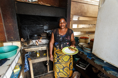 KATIMA MULILO, NAMIBIA - OCTOBER 16 2013: Woman cooks authentic fish dish in food market during a year of drought in the North Eastern town of Katima Mulilo in Namibia, Africa