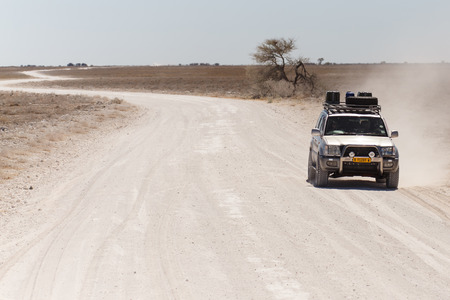 dirt road: ETOSHA, NAMIBIA - OCTOBER 27 2013: Safari Truckdrives on dusty road in a year of drought at Etosha National Park, Namibia, Africa Editorial