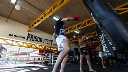 part prison: THAILAND - FEBUARY 11 2014: International fighters take part in warmup training for the upcoming Prison Fight round 6 competition in Khlong Phai Prison, Thailand Editorial