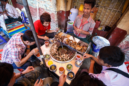 hottest: YANGON, MYANMAR - JUNE 12 2015: Locals eat pot street food on one of the hottest recorded days before monsoon season in Yangon, Myanmar.