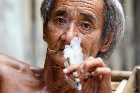 street wise: YANGON, MYANMAR - JUNE 12 2015: Old man smoking burmese cheroot cigar on one of the hottest recorded days before monsoon season in Yangon, Myanmar.