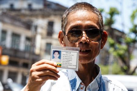 meditator: YANGON, MYANMAR - JUNE 12 2015: Military man holding id card on one of the hottest recorded days before monsoon season in Yangon, Myanmar.