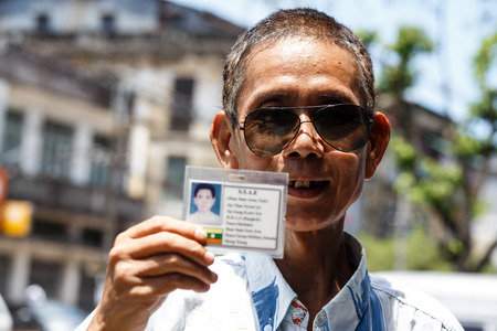 YANGON, MYANMAR - JUNE 12 2015: Military man holding id card on one of the hottest recorded days before monsoon season in Yangon, Myanmar.