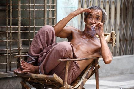 recorded: YANGON, MYANMAR - JUNE 12 2015: Old man smoking burmese cheroot cigar on one of the hottest recorded days before monsoon season in Yangon, Myanmar.