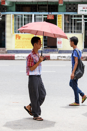 hottest: YANGON, MYANMAR - JUNE 12 2015: Man takes shade under umbrella on one of the hottest recorded days before monsoon season in Yangon, Myanmar.