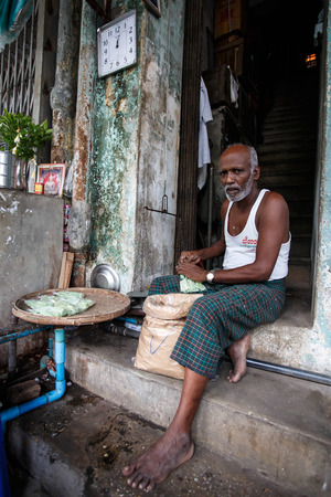 hottest: YANGON, MYANMAR - JUNE 12 2015: Local man making sweet snack on one of the hottest recorded days before monsoon season in Yangon, Myanmar. Editorial