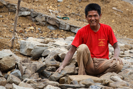 FALAM, MYANMAR - JUNE 17 2015: Local people work hard on construction at Laiva Dam in Chin State, Western Myanmar (Burma) Editorial