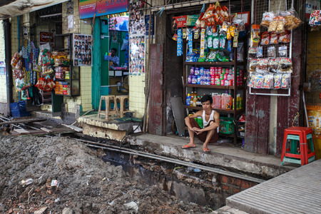 store keeper: YANGON, MYANMAR - JUNE 12 2015: Local store is open on one of the hottest recorded days before monsoon season in Yangon, Myanmar. Editorial