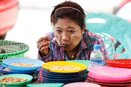 eats: YANGON, MYANMAR - JUNE 12 2015: Local lady eats at market on one of the hottest recorded days before monsoon season in Yangon, Myanmar.