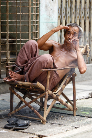 cheroot: YANGON, MYANMAR - JUNE 12 2015: Old man smoking burmese cheroot cigar on one of the hottest recorded days before monsoon season in Yangon, Myanmar.