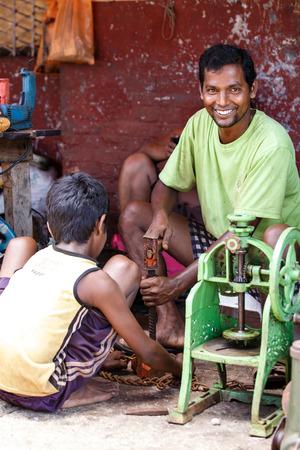 recorded: YANGON, MYANMAR - JUNE 12 2015: Metal worker man on one of the hottest recorded days before monsoon season in Yangon, Myanmar.