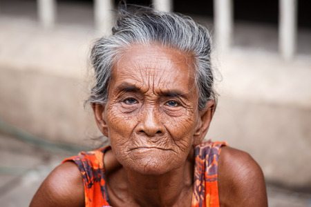 street wise: YANGON, MYANMAR - JUNE 12 2015: Older lady sits on the street on one of the hottest recorded days before monsoon season in Yangon, Myanmar. Editorial
