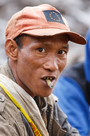 cheroot: FALAM, MYANMAR - JUNE 17 2015: Local man smoking burmese cigar (cheroot) at the start of the monsoon season in the recently opened to tourists Chin State region of Western Myanmar (Burma) Editorial
