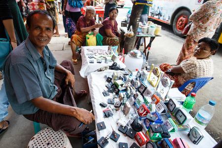 shop keeper: YANGON, MYANMAR - JUNE 12 2015: Clock seller on one of the hottest recorded days before monsoon season in Yangon, Myanmar.