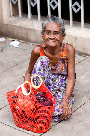 recorded: YANGON, MYANMAR - JUNE 12 2015: Older lady sits on the street on one of the hottest recorded days before monsoon season in Yangon, Myanmar. Editorial