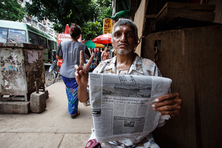 recorded: YANGON, MYANMAR - JUNE 12 2015: Local street man sits on one of the hottest recorded days before monsoon season in Yangon, Myanmar. Editorial