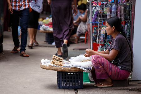 fish selling: YANGON, MYANMAR - JUNE 12 2015: Woman selling small dried fish on one of the hottest recorded days before monsoon season in Yangon, Myanmar.