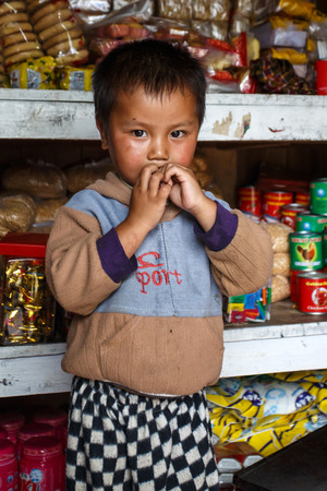 recently: FALAM, MYANMAR - JUNE 17 2015: Local cute boy stands at convenience store entrance at the start of the monsoon season in the recently opened to tourists Chin State region of Western Myanmar (Burma)
