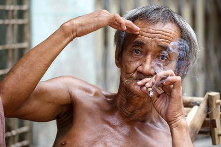 cheroot: YANGON, MYANMAR - JUNE 12 2015: Old man smoking burmese cheroot cigar on one of the hottest recorded days before monsoon season in Yangon, Myanmar.