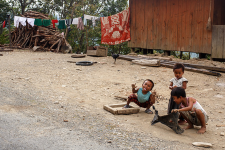 CHIN STATE, MYANMAR - JUNE 16 2015: Children play in the street of a village in the recently opened to foreigners area of Chin State - western Myanmar (Burma)