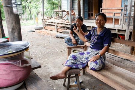 foreigners: CHIN STATE, MYANMAR - JUNE 16 2015: Two ladies sit in a village in the recently opened to foreigners area of Chin State - western Myanmar (Burma)