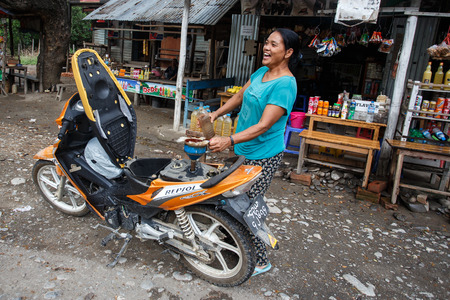 refills: CHIN STATE, MYANMAR - JUNE 16 2015: Lady refills gasoline from a bottle in the recently opened to foreigners area of Chin State - western Myanmar (Burma) Editorial