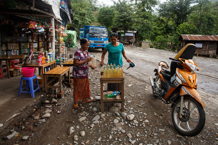 CHIN STATE, MYANMAR - JUNE 16 2015: Lady refills gasoline from a bottle in the recently opened to foreigners area of Chin State - western Myanmar (Burma) Editöryel