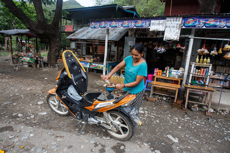 western state: CHIN STATE, MYANMAR - JUNE 16 2015: Lady refills gasoline from a bottle in the recently opened to foreigners area of Chin State - western Myanmar (Burma) Editorial